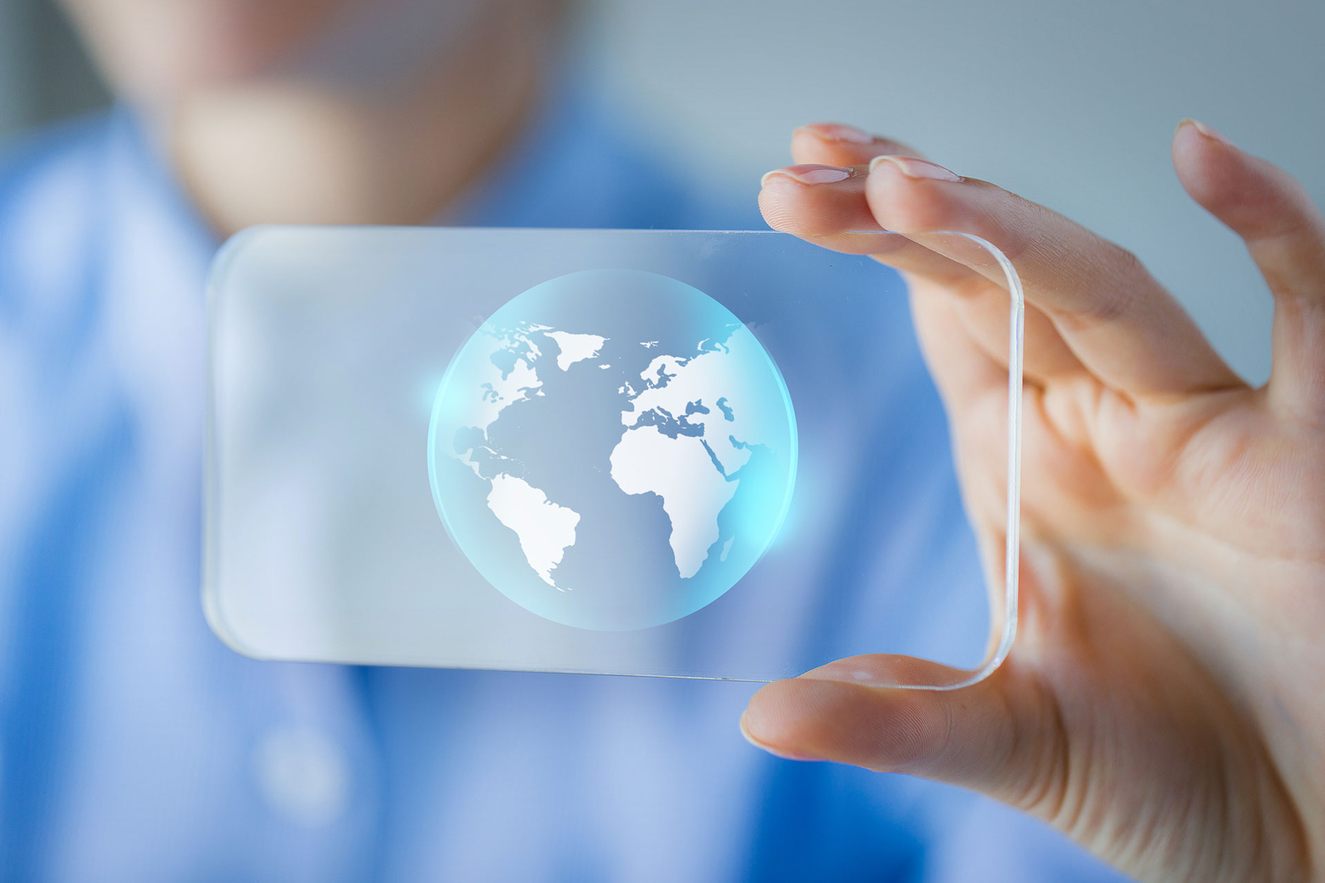 Person holding up a clear screen with a globe