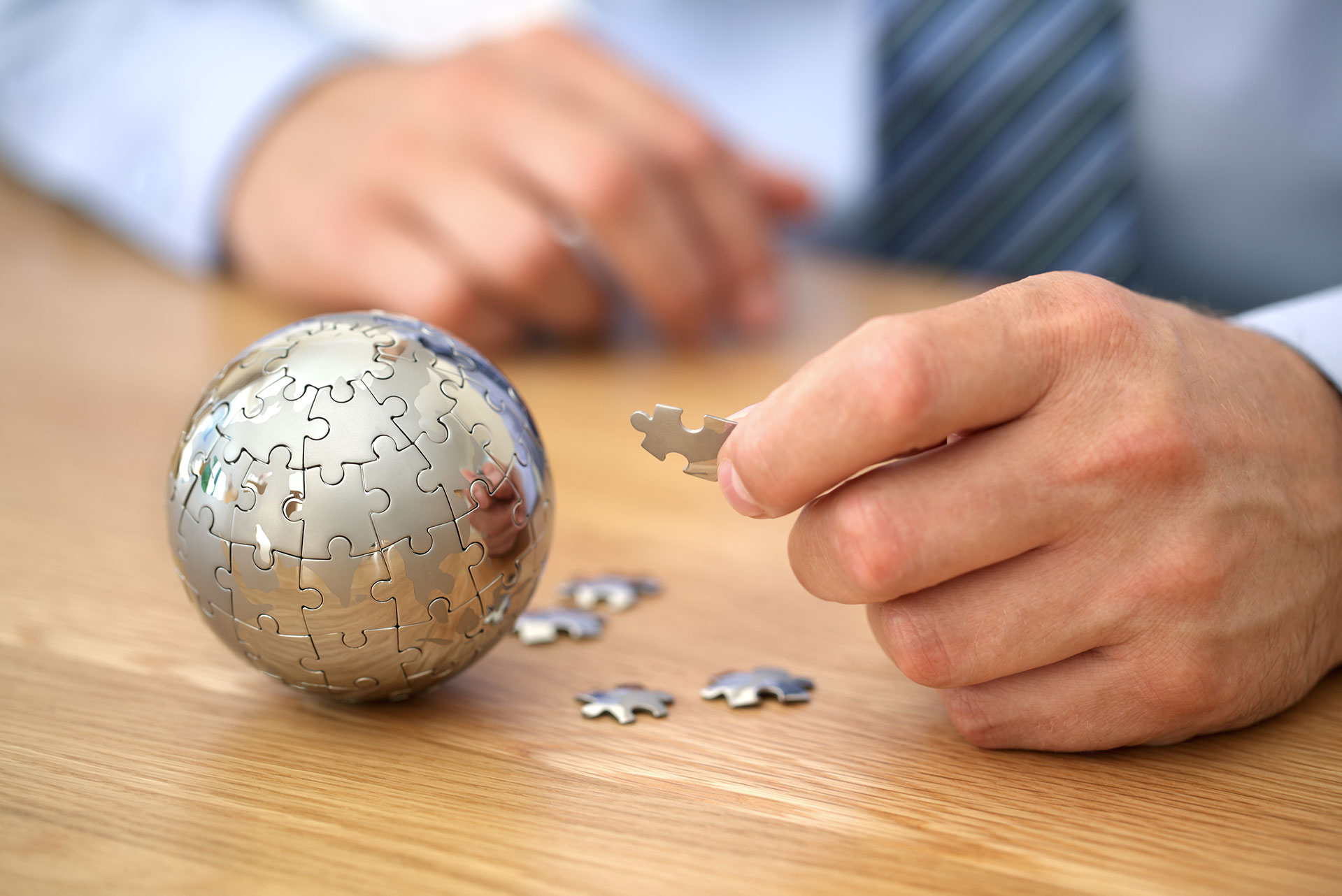 Man putting together a world puzzle