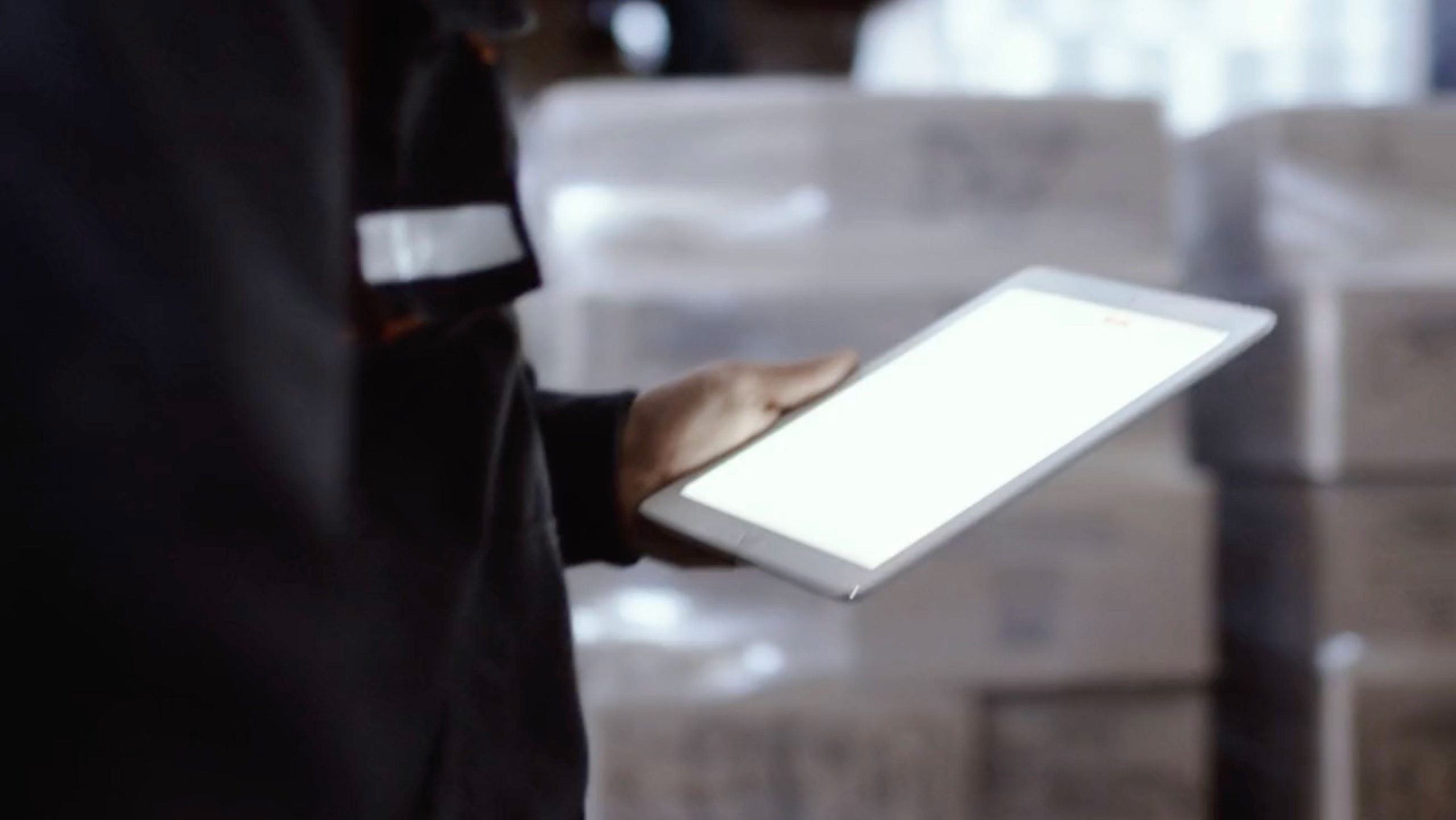 Man holding an Ipad in a warehouse.